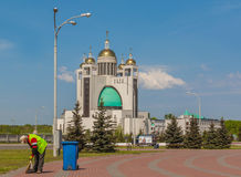 Worker cleans the territory against the backdrop of the Cathedra Royalty Free Stock Photography