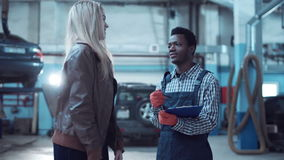 Worker and client in auto service. Car mechanic in uniform writing down information about client in auto service stock footage