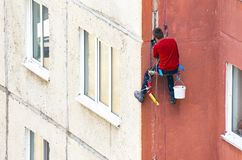 Worker Climber Hanging On Ropes on a High-Rise Building Facade and Sealing Joints. Maintenance of Joints between Precast Concrete. Panels to Prevent Leakage stock photos