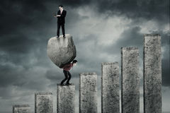 Worker climbing chart with boulder and partner Royalty Free Stock Photography