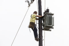 Worker climbing on Electrical concrete pole transmission line Royalty Free Stock Images