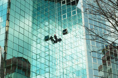 Worker climbing at mirror wall. Of office building Stock Photo