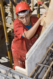 Worker Climbs Ladder - Vertical Stock Photography