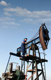 Worker climbs up to the pump jack Royalty Free Stock Photography