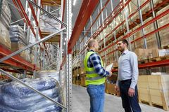 Worker with clipboard and businessman at warehouse. Logistic business, shipment and people concept - worker with clipboard and businessman at warehouse Stock Photography