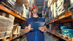 A worker with a clipboard inspects a warehouse. stock footage
