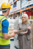 Worker with clipboard speaking with his manager Stock Photo