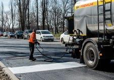 Worker, closing joints before laying asphalt. Rusanovka district. Kiev, Ukraine Stock Photos