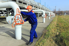 Worker closing valve. On output installations of gas compressor station Stock Photos