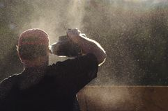 Worker in Cloud of Sawdust Stock Photo