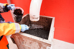 Worker collecting mud from biodegradable waste pool Stock Photos