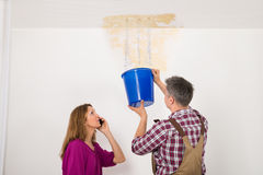 Worker Collecting Water In Bucket From Ceiling. While Woman Talking On Mobile Phone Royalty Free Stock Image