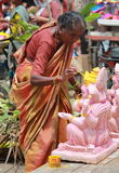 Worker colouring Ganesh idol in hyderabad, India Stock Photo
