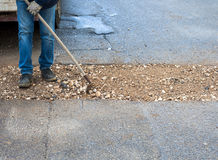 Worker committed to the repair of a large pit road. With inert mixed stabilized Royalty Free Stock Image