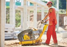 Worker with compaction machine. Builder worker compacting soil with vibration plate compaction machine during pavement roadwork Stock Photography