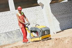 Worker with compaction machine. Builder worker compacting soil with vibration plate compaction machine during pavement roadwork Stock Images