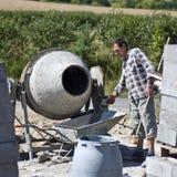 Worker and concrete mixer Stock Photos