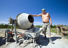 Worker and concrete mixer. A worker standing at a concrete mixer, pouring concrete into a wheelbarrow Stock Images