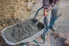 Worker with concrete mortar in wheelbarrow Stock Images
