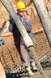 Worker on concrete works. Builder worker aiming pump tube during concrete pouring process at construction site stock image