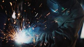 Worker connects parts by welding in dark workshop closeup stock video footage