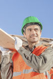 Worker construction carrying wood plank Royalty Free Stock Images