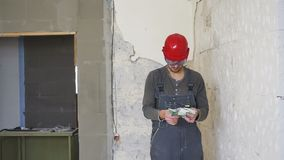 The worker in a construction with helmet counts money euro against the background of the repaired apartment. The worker in a construction with helmet counts stock video footage