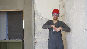 The worker in a construction with helmet counts money euro against the background of the repaired apartment. The worker in a construction with helmet counts stock video