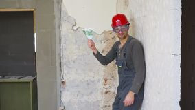 The worker in a construction with helmet counts money euro against the background of the repaired apartment. The worker in a construction with helmet counts stock footage