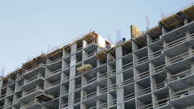 Worker at the construction site. A worker at a construction site is building a house stock footage