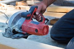 Worker at a construction site with a circular saw royalty free stock photo