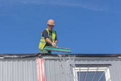 Worker at the construction site cleans the roof royalty free stock photos