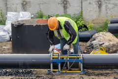 Worker at the construction site connects the pipes royalty free stock photography