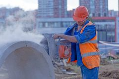 Builder with a concrete cutter royalty free stock image