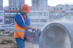 Worker cuts the concrete ring royalty free stock photo