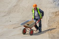 Worker at the construction site loads the shovel with sand in the wheelbarrow stock photos