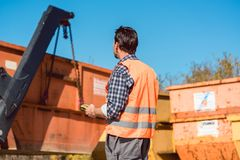 Worker on construction site unloading container for waste from t. Ruck using remote control Stock Image