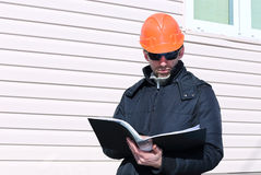 Worker on a construction site in winter looks at the drawing Royalty Free Stock Photography