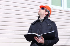 Worker on a construction site in winter looks at the drawing Royalty Free Stock Image
