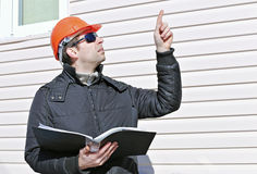 Worker on a construction site in winter looks at the drawing and shows up finger Stock Photos