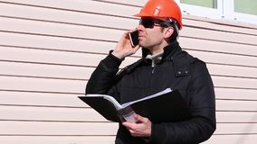 Worker on a construction site in winter talking on smartphone stock footage