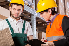 Worker consulting with manager in warehouse Stock Photos