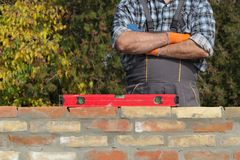 Worker examining brick wall. Worker control brick wall using level tool, real people, no retouch Royalty Free Stock Photo