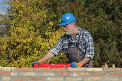 Worker examining brick wall. Worker control brick wall using level tool, real people, no retouch Stock Image