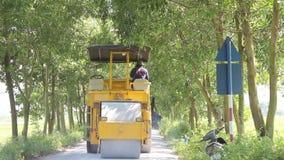 Worker control steamroller working in road stock video