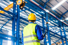 Worker controlling crane with remote. Worker in factory controlling crane with remote Stock Photo