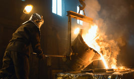 Worker controlling metal melting in furnaces. Workers operates at the metallurgical plant. Royalty Free Stock Photography