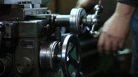 Worker controls adjustment wheel of lathe machine stock footage