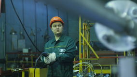 Worker controls mechanism using wired remote control. KAZAN, TATARSTAN/RUSSIA - JUNE 12 2016: Shop worker controls mechanism using wired remote control and stock footage