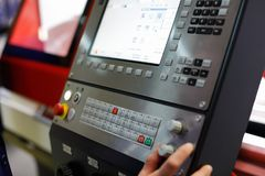 Worker controls the operation of the CNC machine. The worker controls the operation of the CNC machine using the control panel and the display. Selective focus Stock Photo